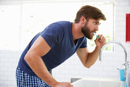Man In Pajamas Brushing Teeth In Bathroom