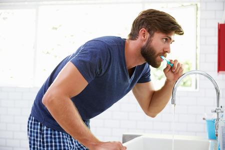Man In Pajamas Brushing Teeth In Bathroom