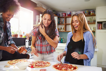 woman cooking: Three Female Friends Making Pizza In Kitchen Together Stock Photo
