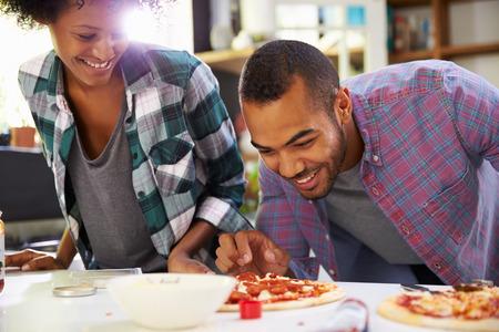 Jong Paar dat Pizza in Keuken samen Stockfoto