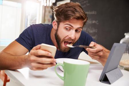 comiendo cereal: El hombre que come el desayuno durante el uso de la tableta digital y teléfono