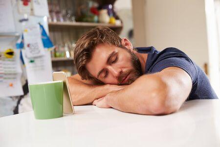 agotado: Hombre Cansado Dormido En La Cocina mesa junto a Teléfono Móvil