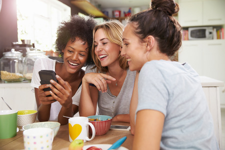 three friends: Female Friends Eating Breakfast Whilst Checking Mobile Phone Stock Photo