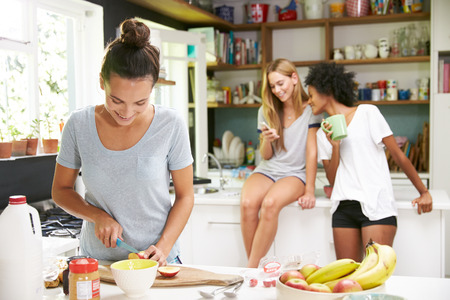 whilst: Female Friends Making Breakfast Whilst Checking Mobile Phone
