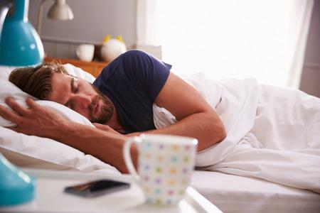 Schlafende Mann, der mit dem Handy im Schlafzimmer geweckt