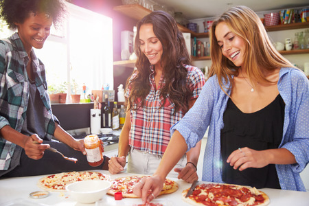 preparing food: Three Female Friends Making Pizza In Kitchen Together Stock Photo