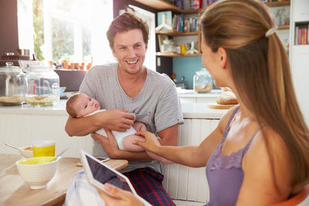 Family With Baby Girl Use Digital Tablet At Breakfast Table