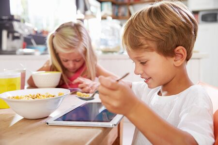 ni�os desayunando: Ni�os que comen el desayuno mientras que usa la tablilla digital