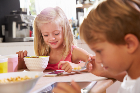 whilst: Children Eating Breakfast Whilst Playing With Mobile Phone