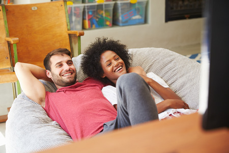 couple relaxing: Young Couple In Pajamas Watching Television Together Stock Photo