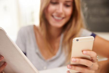 Žena doma s digitální tablet a mobilní telefon