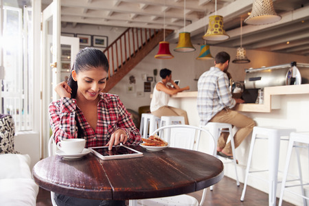 tablet: Young woman using laptop in a cafe