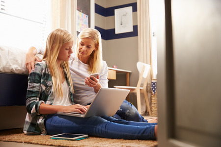 woman sitting with laptop: Mother and daughter spending time together at home