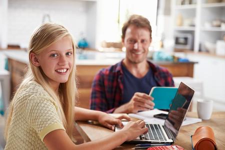 deberes: Padre e hija usando la computadora portátil en casa