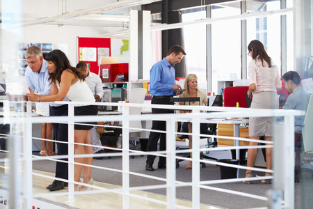 trabajo en oficina: El personal que trabaja en una oficina ocupada entrepiso