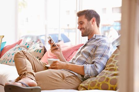 Junger Mann sitzt auf dem Sofa in einem Café Standard-Bild - 41392484