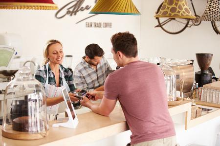 pagando: Hombre joven que paga por su orden en una cafetería