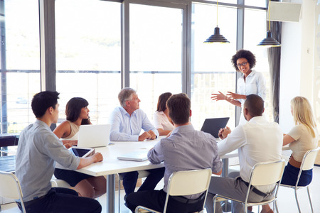 an office work: Empresaria que presenta a sus colegas en una reunión Foto de archivo