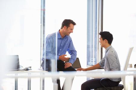 Twee mannen praten in een modern kantoor