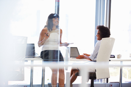 three people only: Two women talking in an office Stock Photo