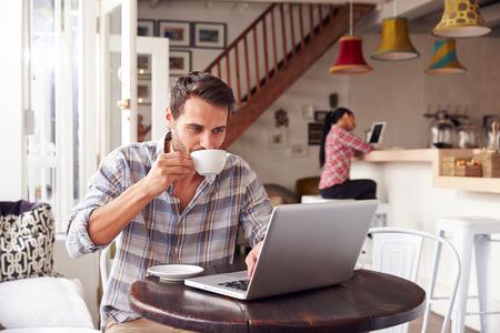 hombre tomando cafe: Hombre joven que usa la computadora port�til en un caf�