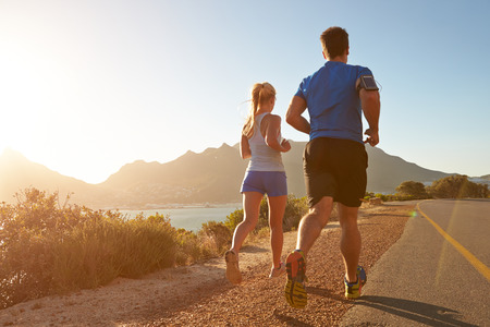 hombres corriendo: El hombre y la mujer corriendo juntos en una carretera vac�a Foto de archivo
