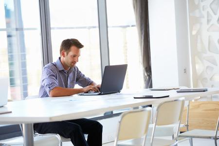 オフィスで一人で働く男