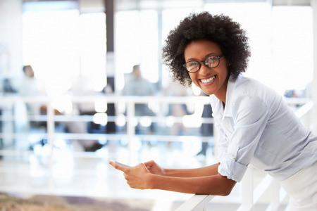 Portrait of smiling woman in office with telephone Foto de archivo