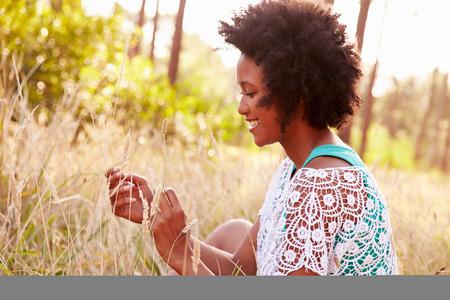 personas saludables: Retrato de la mujer sonriente joven que se sienta en Campo Foto de archivo