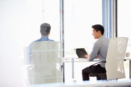 usando computadora: Dos personas que trabajan en una oficina moderna