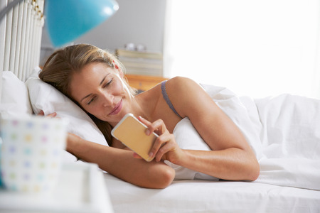 a check: Woman Lying In Bed Reaching To Check Mobile Phone