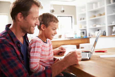 Father and son using laptop computer at home Stock Photo