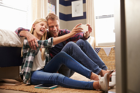 Father and daughter taking selfie together photo