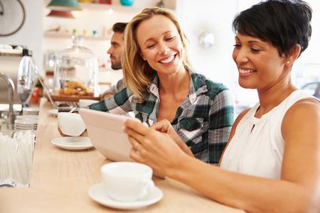 mujer: Dos mujeres en una reunión en un café