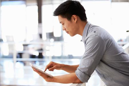 personas leyendo: Retrato de hombre joven que usa la tableta en una oficina Foto de archivo