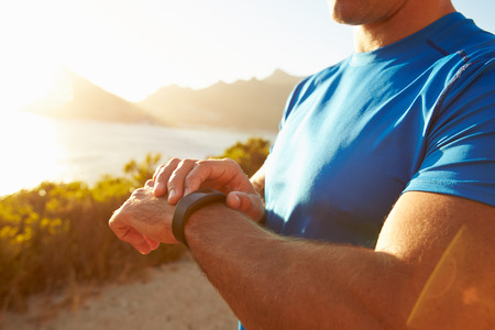 deporte: Hombre joven que controla tiempo en su reloj deportivo