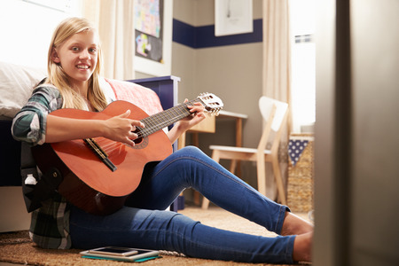 Girl playing guitar in her bedroom photo