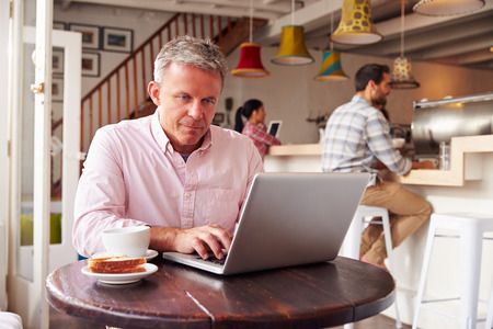 Middle aged man using laptop in a cafe Imagens