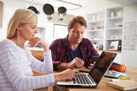 コンピューターを使用して彼らの台所に座っている重点を置かれたカップル 写真素材