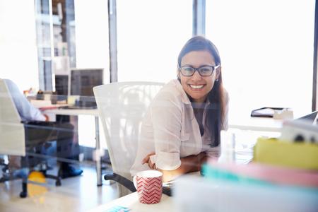 personas trabajando: Mujer en su escritorio en una oficina sonriendo a la cámara