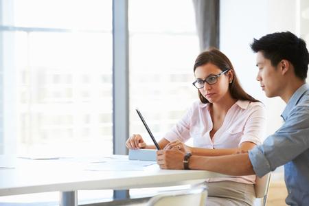 gente trabajando: Dos personas que trabajan con la tableta digital en la sala de reuniones vacía