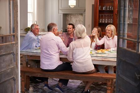 家で一緒に食事を楽しんで友人のグループ 写真素材