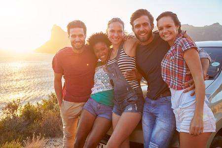 route: Groupe d'amis debout En voiture sur la route côtière au coucher du soleil