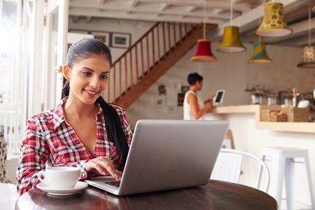 personas mirando: Mujer joven que usa la computadora portátil en un café