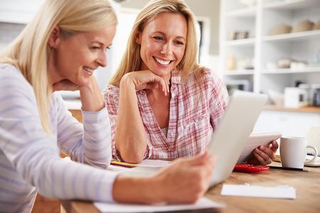 femmes souriantes: Deux femmes qui travaillent ensemble à la maison Banque d'images