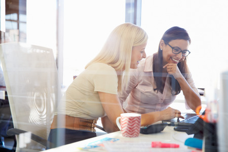 dos personas hablando: Mujeres trabajando juntos, interior de la oficina
