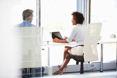 dos personas platicando: Dos personas que trabajan en una oficina moderna