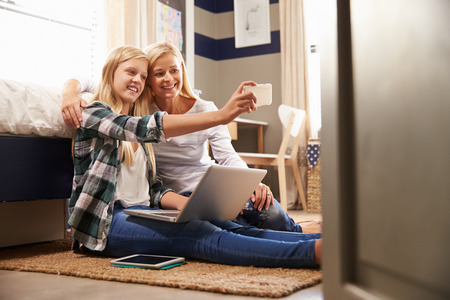 preteens girl: Mother and daughter taking selfie together at home