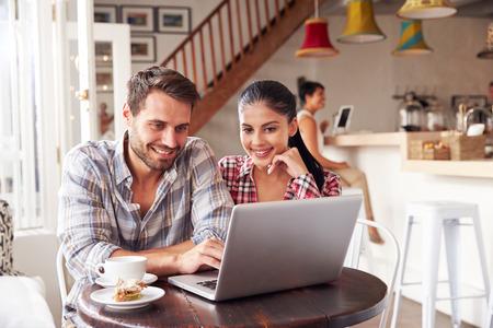 hombres trabajando: Pareja joven usando la computadora portátil en un café Foto de archivo
