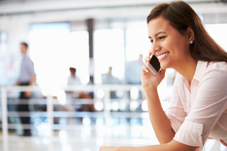 confident woman: Portrait of smiling woman in office with telephone Stock Photo
